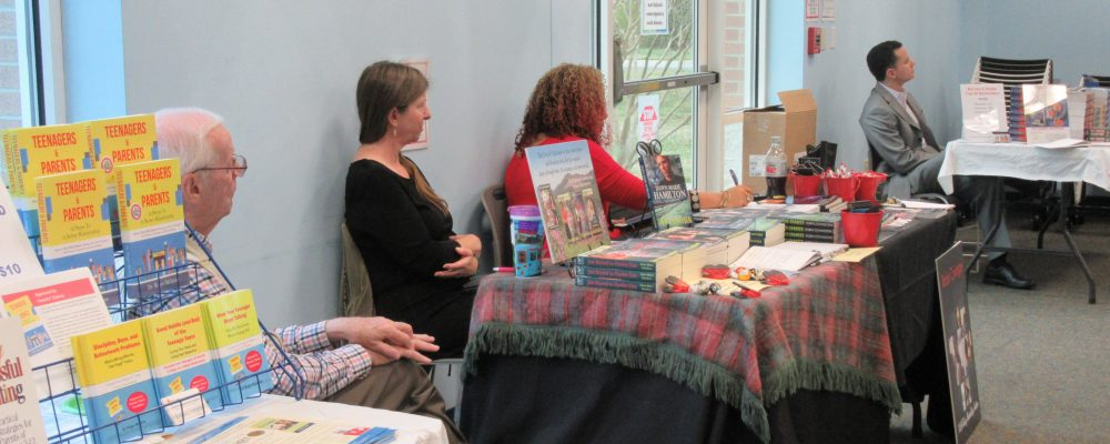 Three tables at the 2017 author fair, with books on display and 4 authors sitting at the tables