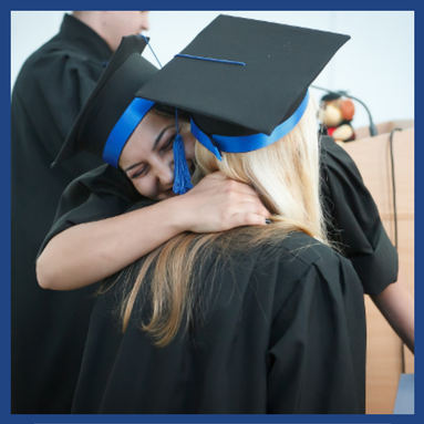 two graduates in cap and gown hugging