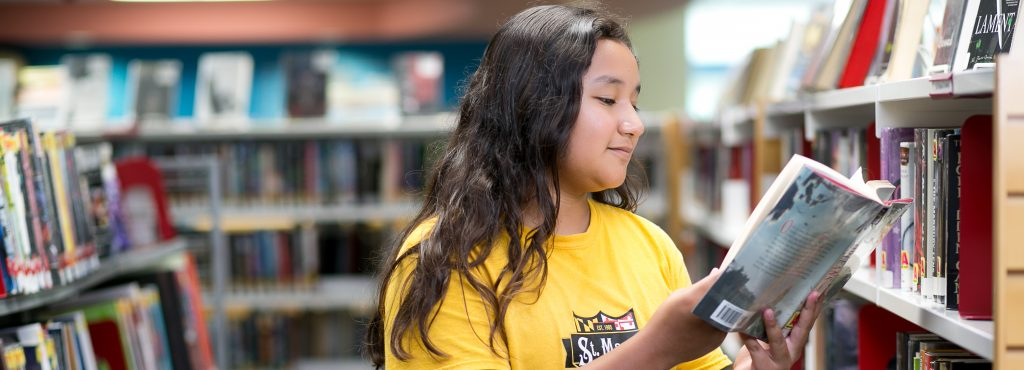 teen girl in yellow shirt reading a book