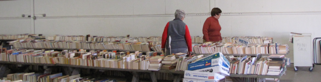 two women sorting stacks of donated books on long tables