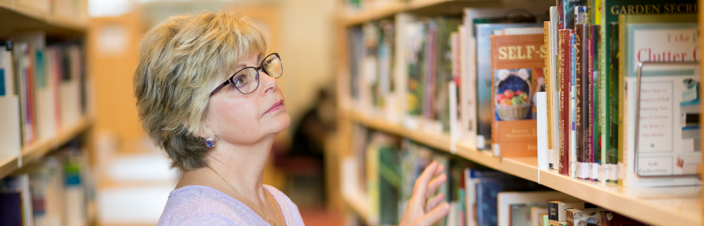 woman with glasses looking at a shelf of books