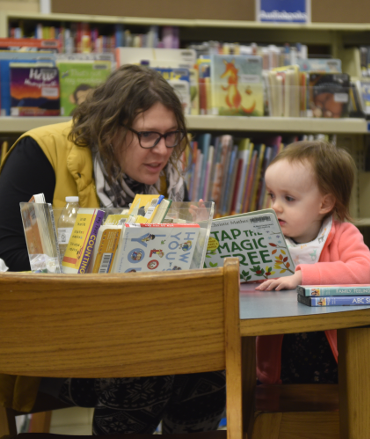 Mother and child sitting at a table reading a board book
