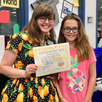 librarian and a young girl holding an honorary MLS certificate
