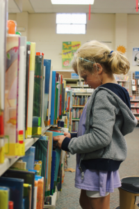 Girl in grey sweatshirt browsing library shelves