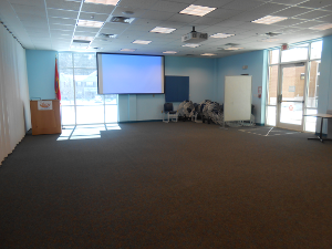 Picture of empty Lexington Park meeting room B with projector screen at front