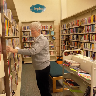 woman looking at book shelves with a cart of books behind her