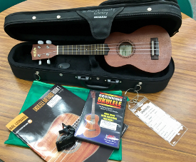 Photo of open case with ukulele inside and ukulele book and DVD on a table beside the case