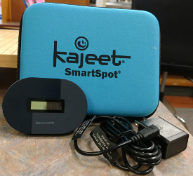 Blue square case with Kajeet SmartSpot printed in black. Oval shaped hotspot approximately 2 inches by 3.5 inches and black AC charger