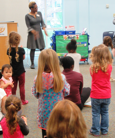 A group of children and adults, some sitting and some standing, watching a storytime presenter.