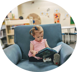 little girl reading a book in a blue chair