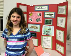 Girl standing in front of a science fair project about snakeheads