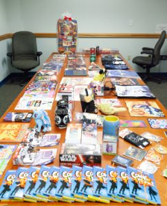 conference table covered in comic books and other prizes
