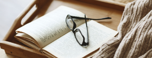 an open book with a pair of glasses sitting on it