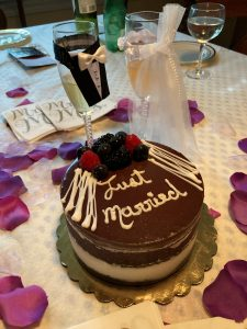 Wedding Cake with chocolate icing reading Just Married, bride and groom champagne glasses