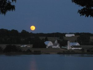 Bright yellow moon in a dark sky over water with farm in the backgroun