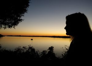 silhouette of a woman in front of a body of water at sunset
